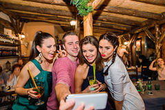 Young beautiful people with cocktails in bar taking selfie Stock Image