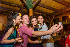 Young beautiful people with cocktails in bar taking selfie Royalty Free Stock Photo