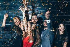 Young beautiful people dancing in confetti. Party fun. New year, Birthday, Holiday Event concept royalty free stock images