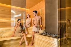 Young and beautiful people smiling while socializing in a wooden dry sauna. Full length of three young and beautiful people smiling while socializing in a wooden Royalty Free Stock Photos