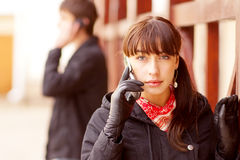 Young beautiful people talk on cellular telephone Royalty Free Stock Photo
