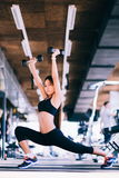 Young beautiful petite woman doing exercises with dumbbell in gym Royalty Free Stock Image