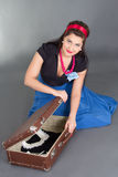 Young attractive pinup girl packing retro suitcase Royalty Free Stock Photography