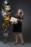 Young beautiful plus size model in black dres with gift box, xxl woman on gray studio background Royalty Free Stock Image
