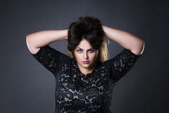 Young beautiful plus size model in black lace dres, xxl woman portrait on gray studio background Royalty Free Stock Image