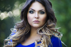 Young beautiful plus size model in blue dress outdoors, confident woman on nature, professional makeup and hairstyle, close-up por Royalty Free Stock Photography