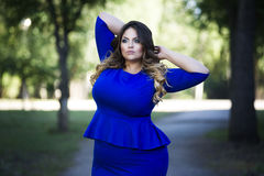 Young beautiful plus size model in blue dress outdoors, xxl woman on nature Royalty Free Stock Photography