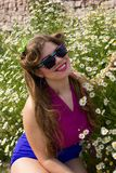 Young beautiful plus size model among flowers outdoors. Young beautiful plus size model in sunglasses among flowers outdoors in summer Royalty Free Stock Images