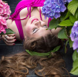 Young beautiful plus size model lying in flowers, professional m. Young beautiful plus size model lying in flowers, xxl woman portrait, professional makeup and Royalty Free Stock Photos