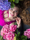 Young beautiful plus size model lying in flowers, xxl woman Stock Photo