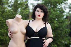 Young beautiful plus size modelt in black bra holding mannequin. Young beautiful busty curvy  plus size model with big breast in black bra holding mannequin, xxl Stock Images