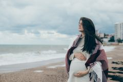 Young beautiful pragnant woman posing near sea at the beach Stock Photography