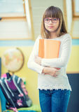 Young of beautiful pre-teen girl with booklet. A child doing homework Royalty Free Stock Images