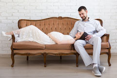 Young beautiful pregnant couple on vintage sofa Stock Photography