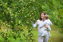 Young beautiful pregnant mother and her baby daughter Stock Photos