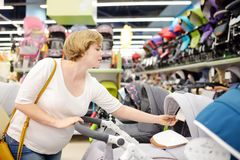 Young beautiful pregnant woman choosing baby stroller or pram buggy for newborn. Shopping for expectant mothers and baby. Pregnancy and shopping stock images