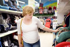 Young beautiful pregnant woman choosing infant car seat. Shopping for expectant mothers and baby. Young beautiful pregnant woman carefully choosing infant car stock photography