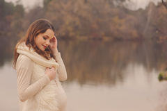 Young beautiful pregnant woman on cozy warm walk on autumn riverside, warm toned, soft focus Stock Image