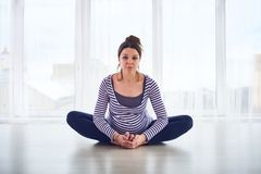 Young beautiful pregnant woman doing yoga asana Baddha Konasana at home. stock photos