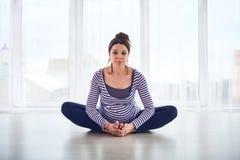 Young beautiful pregnant woman doing yoga asana Baddha Konasana at home. Stock Photos