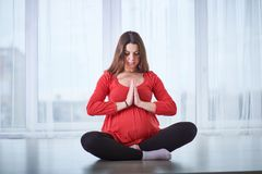 Young beautiful pregnant woman doing yoga asana Padmasana - lotus pose at home. stock photo