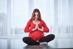 Young beautiful pregnant woman doing yoga asana Padmasana - lotus pose at home. Stock Photo