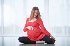 Young beautiful pregnant woman doing yoga asana Vamadevasana - Pose for the Vamadeva at home. royalty free stock image