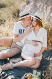 Young beautiful pregnant woman having picnic with her husband on a mountain near sea stock photos