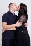 Young beautiful pregnant woman and her husband kissing over grey Royalty Free Stock Images