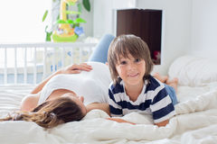 Young beautiful pregnant woman and her sweet child, cuddling wit Royalty Free Stock Image