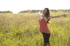 Young beautiful pregnant woman holding tummy smiling, in red a light summer dress, happy on meadow the grass. Young beautiful pregnant woman happy with open arms Stock Photography