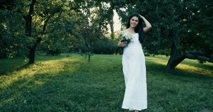 Young beautiful pregnant woman with long brown hair in white dress. 4k. Slow Motion stock video