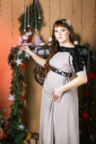 Young beautiful pregnant woman in a long  dress near new year tr Stock Images