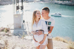 Young beautiful pregnant woman posing with her husband on a mountain Royalty Free Stock Photography