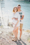 Young beautiful pregnant woman posing with her husband on a mountain Royalty Free Stock Images