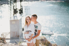 Young beautiful pregnant woman posing with her husband on a mountain Royalty Free Stock Photos