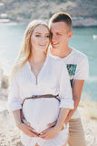 Young beautiful pregnant woman posing with her husband on a mountain Royalty Free Stock Photo