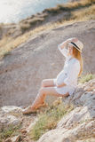 Young beautiful pregnant woman posing on a mountain near sea Stock Photography