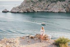 Young beautiful pregnant woman posing on a mountain near sea Royalty Free Stock Photos