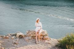 Young beautiful pregnant woman posing on a mountain near sea Royalty Free Stock Images
