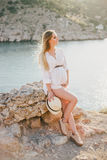 Young beautiful pregnant woman posing on a mountain near sea Royalty Free Stock Photography