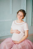 Young beautiful pregnant woman posing near window Royalty Free Stock Images