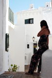 Young beautiful pregnant woman relaxing herself in the wonderful white walled streets of a mediterranean village in Menorca Island Stock Photo