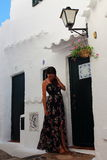 Young beautiful pregnant woman relaxing herself in the wonderful white walled streets of a mediterranean village in Menorca Island Royalty Free Stock Photo