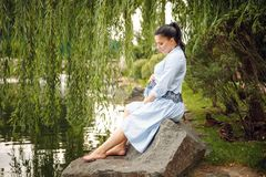 Young beautiful pregnant woman relaxing on the rocks by the lake on the background in summer royalty free stock photos