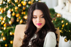 Young beautiful pregnant woman siting in a Christmas setting. Royalty Free Stock Photo