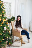 Young beautiful pregnant woman siting in a Christmas setting. Stock Images