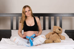 Young beautiful pregnant woman sitting on a bed Royalty Free Stock Photo