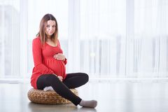 Young beautiful pregnant woman sitting on windowsill at home royalty free stock photo