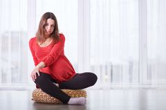 Young beautiful pregnant woman sitting on windowsill at home Stock Images